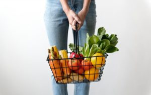 Woman holding wire shopping basket full of fresh fruit and veg